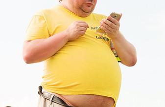 obese man in yellow shirt checking phone